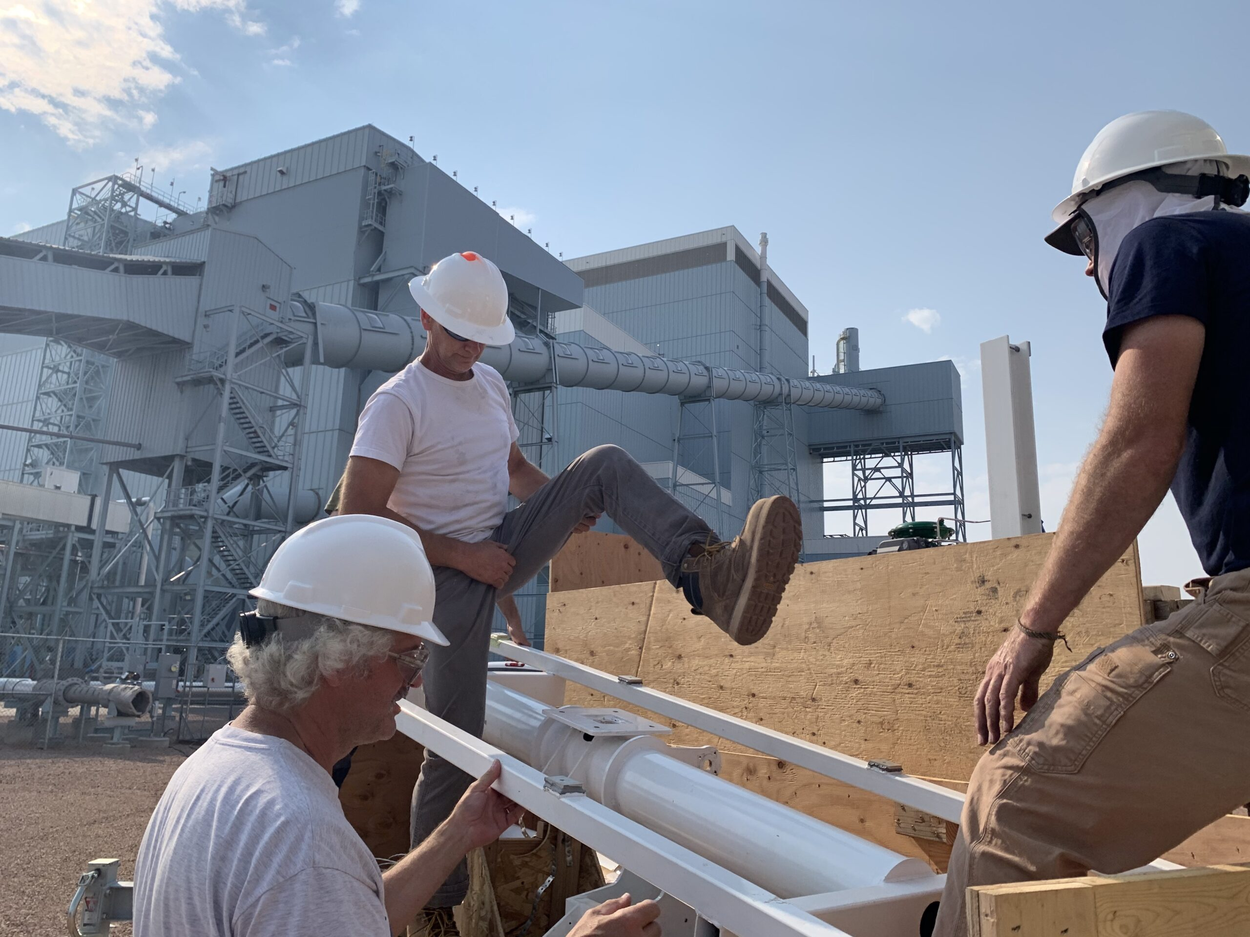 (From Left To Right) Brian Bowman, Jason Salfi, and Huck Milton removing part of the solar tracker from the trailer